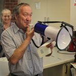 John demonstrates the correct way to use a bullhorn